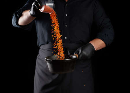 chef in black clothes and latex gloves pours raw lentils into a round cast iron pan with a handle, black background Banque d'images
