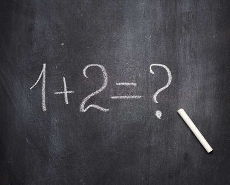 math example written in white chalk on a black chalk board and white chalk, one plus two
