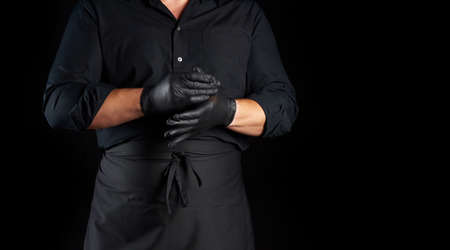 chef in black shirt and apron puts black latex gloves on his hands before preparing food, black background, copy space