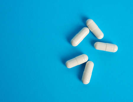 white capsules on a blue background, top view of pills, close up Stock fotó - 154845665