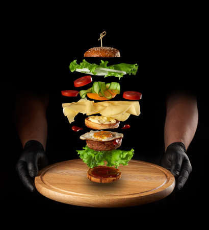 round wooden board and layers of a large cheeseburger floating in the air: meat cutlet, lettuce, fried egg, tomato and cucumber slices, black background