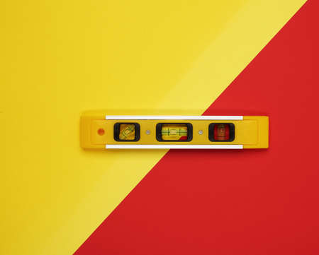 plastic yellow level tool with capsules on red background, close up