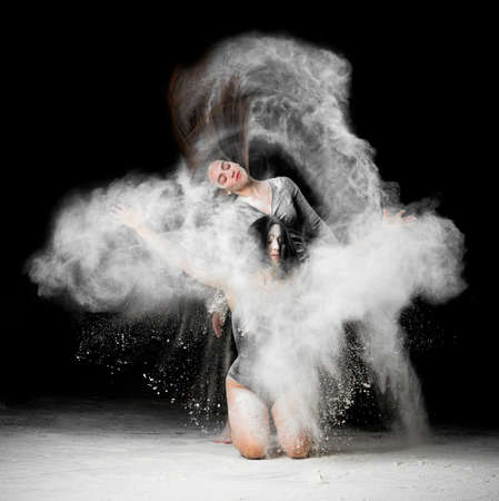 two beautiful young caucasian women in black bodysuits with a sports figure are dancing in a white cloud of flour on a black background, explosion and expresse in motion Фото со стока
