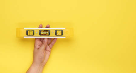 female hand hold plastic yellow level tool with capsules on a yellow background, copy space Banco de Imagens