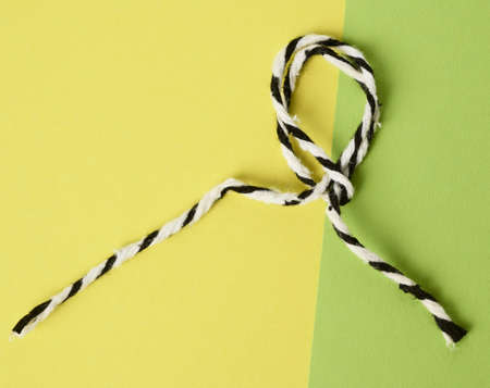 white-black rope on a green background twisted into a loop, close up