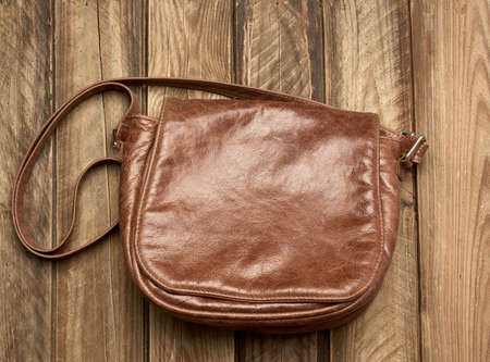 brown leather bag on gray wooden background, top view