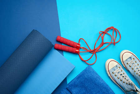 twisted blue mat, a pair of blue gym shoes and a red skipping rope for jumping on a blue background, set for sports, copy space
