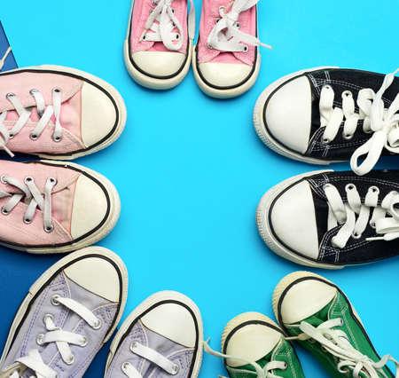 many multi-colored well-worn textile sneakers of different sizes on a blue background, top view, concept, family and team, friendship Standard-Bild