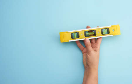 female hand hold plastic yellow level tool with capsules on a blue background, copy space