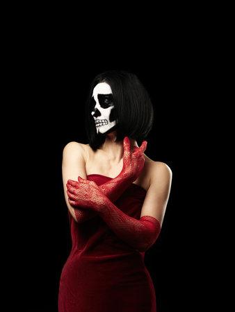 woman of Caucasian appearance dressed in a red velvet dress, long fishnet gloves. Halloween Skeleton Makeup, Black Background