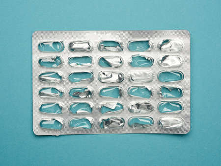 blank blister pack of capsule pills on a blue background, top view 版權商用圖片
