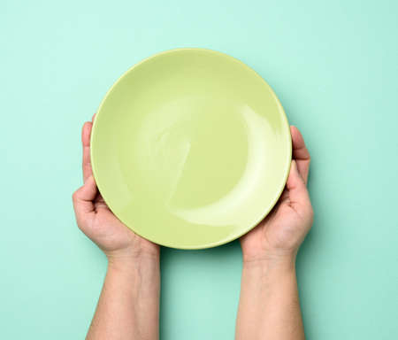 two hands holding a round empty green plate, top view