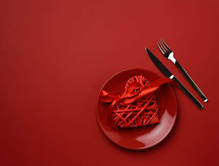 round ceramic plate and fork with knife on red background, festive table setting, top view