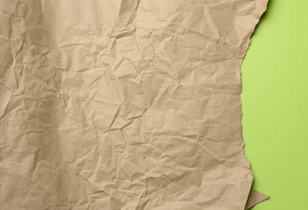 empty sheet of brown wrapping kraft paper, texture for the designer, torn edge on green background Фото со стока