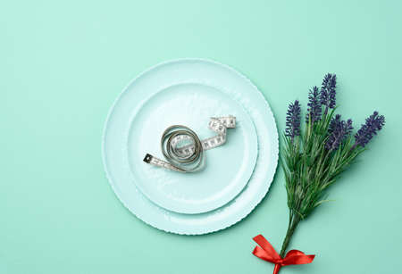 round ceramic plate and centimeter on green background, slimming concept, top view Фото со стока