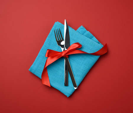metal fork and knife tied with a red silk ribbon, red background, top view