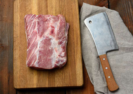 knife and raw pork tenderloin on a wooden cutting board, top view Фото со стока