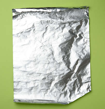 gray foil for baking and packaging food on a green background, top view, copy space