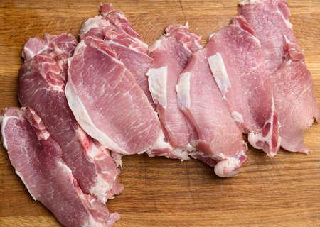 sliced pork tenderloin on a wooden cutting board, top view