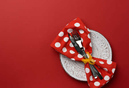 white round ceramic plates, fork with knife on a red background, top view. Table setting, copy space