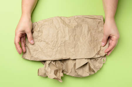 two hand holds piece of crumpled brown paper on a green background, element for designer, top view Фото со стока