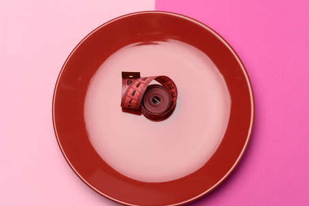 twisted red centimeter in a red plate, top view