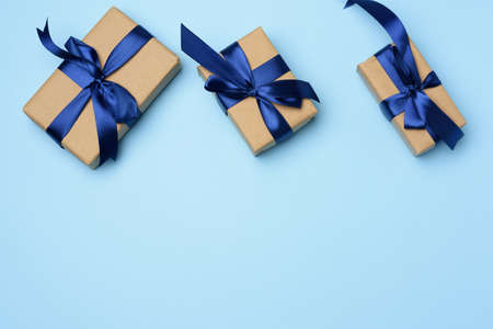 rectangular box wrapped in brown paper and tied with a blue silk ribbon with a bow, gift on a blue background, top view, copy space Фото со стока