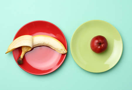 red ripe apple and banana lie in a round ceramic plate, top view, healthy food Фото со стока