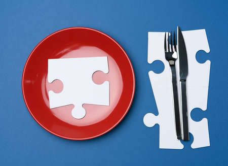 red round ceramic plates, fork with knife on a blue background, top view. Table setting