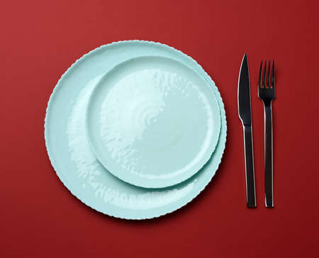 round ceramic plates, fork with knife on a red background, top view. Table setting