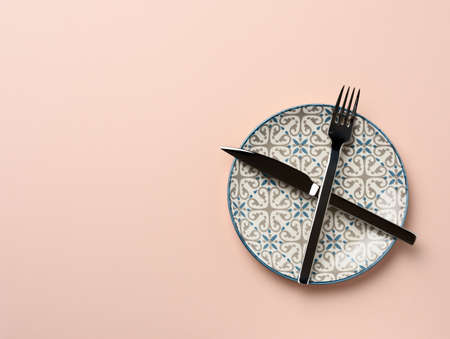 round ceramic plate and crossed knife and fork on beige background, top view Stok Fotoğraf