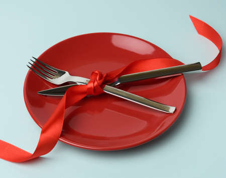 round plate and metal fork and knife tied with a red silk ribbon, blue background, place for an inscription, top view