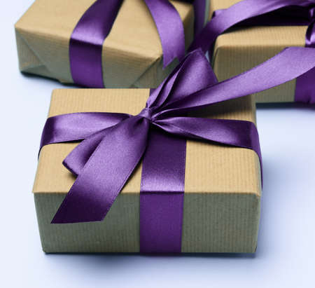 box wrapped in brown paper and tied with a purple silk ribbon with a bow, gift on a blue background, top view,