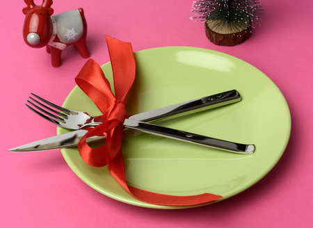 round green plate and metal fork and knife tied with a red silk ribbon, pink background