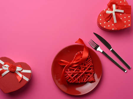 gift box and round ceramic plate and fork with knife on a pink background, festive table setting, top view