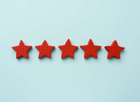 five red wooden stars on a blue background, high score, rating Фото со стока