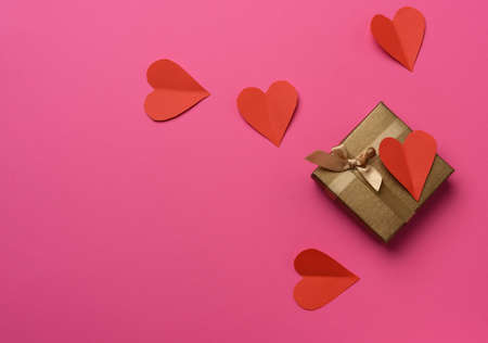 gift box wrapped in brown paper and red paper heart, box on a pink background, top view,