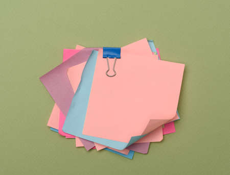 stack of colorful paper stickers on green background, close up Фото со стока