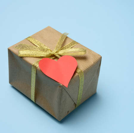 gift box wrapped in brown paper and red paper heart, box on a blue background, top view, Фото со стока