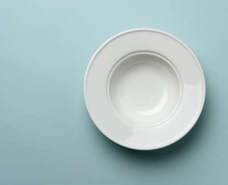 empty white ceramic plate on blue background, top view