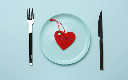 red heart lies in a blue round ceramic plate, next to a fork and a knife, top view Фото со стока