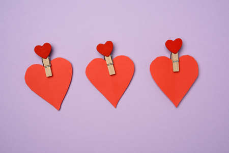 red paper heart pinned on a wooden clothespin, purple background, flat lay Фото со стока