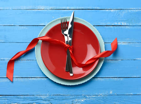 round plate and metal fork and knife tied with a red silk ribbon, blue wooden background, top view