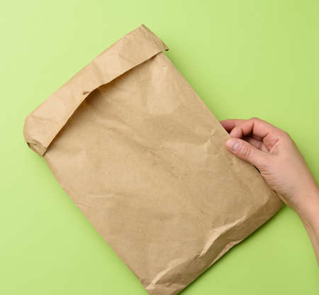 two hands holding a paper bag of brown kraft paper ona green background, top view