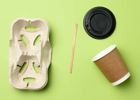 disposable paper cups from brown craft paper and recycled paper holders on a green background, top view, plastic rejection concept, zero waste