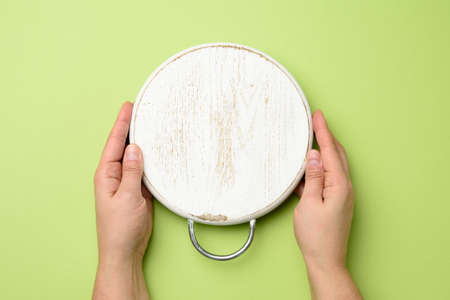 woman hand holding white empty round wooden board in hand, green background, top view Фото со стока