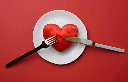 red heart lies in a white ceramic plate on a red background, next to a fork and a knife, top view