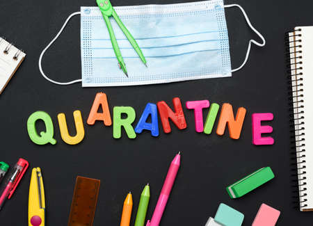 inscription quarantine from multicolored plastic letters and school supplies on black chalk board, concept of closing schools during a pandemic Фото со стока