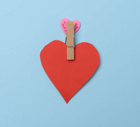 red paper heart pinned on a wooden clothespin, blue background, flat lay Фото со стока