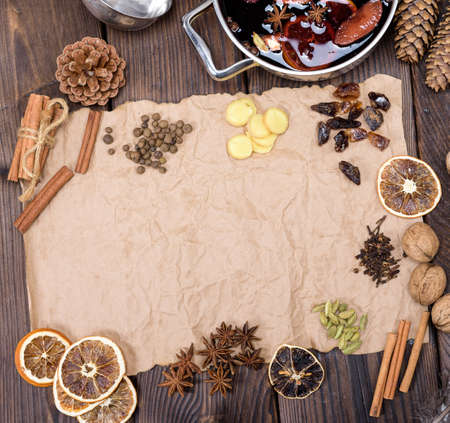 ingredients for making mulled wine on a wooden table and a piece of brown paper to write the recipe, top view, copy space